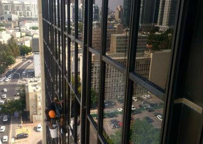 ניקוי חלונות בגובה עם ציוד סנפלינג מקצועי